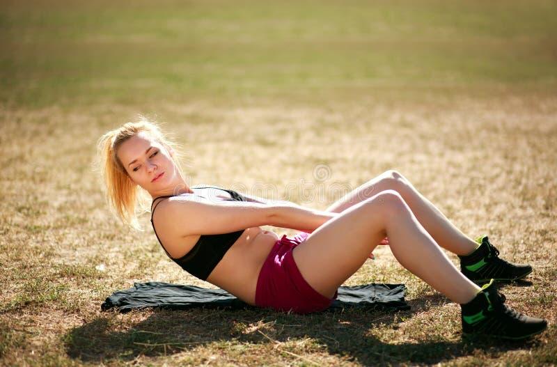 Mujer que hace aptitud abdominal del ejercicio al aire libre fotografía de archivo libre de regalías