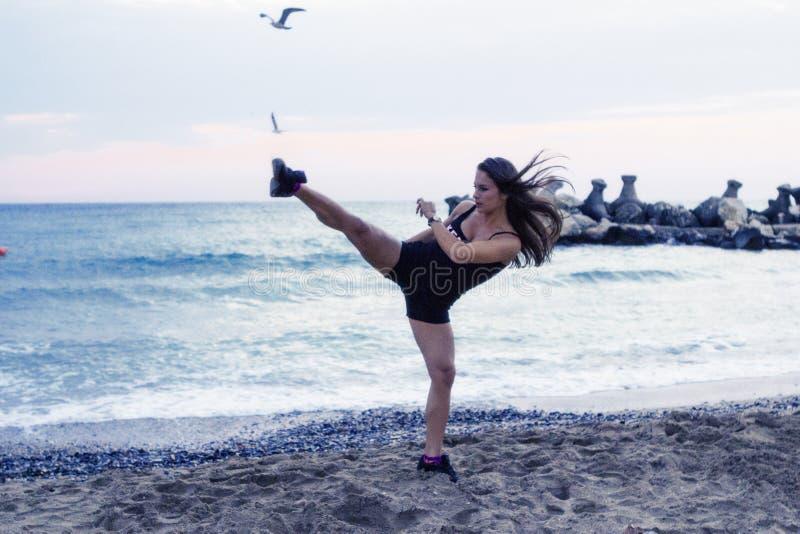 Mujer que hace artes marciales en la playa fotos de archivo