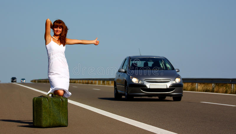 Mujer que hace autostop en una carretera imagen de archivo