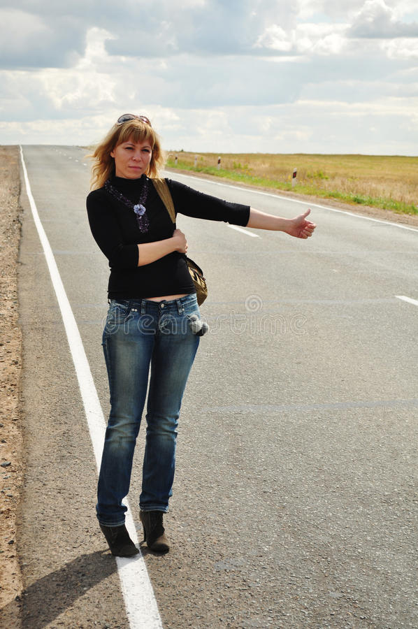 Mujer que hace autostop, viaje por carretera foto de archivo