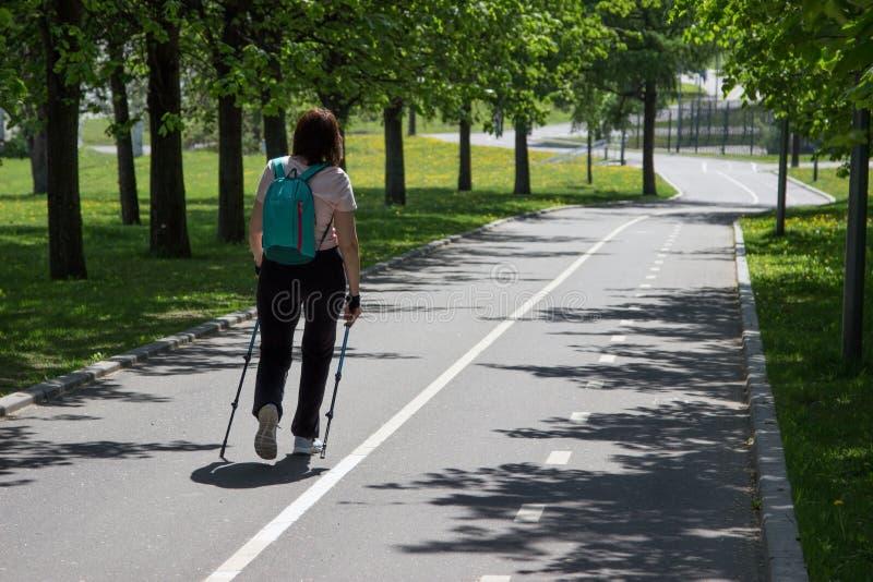 Mujer que hace caminar nórdico con un parque del verano en un día soleado foto de archivo
