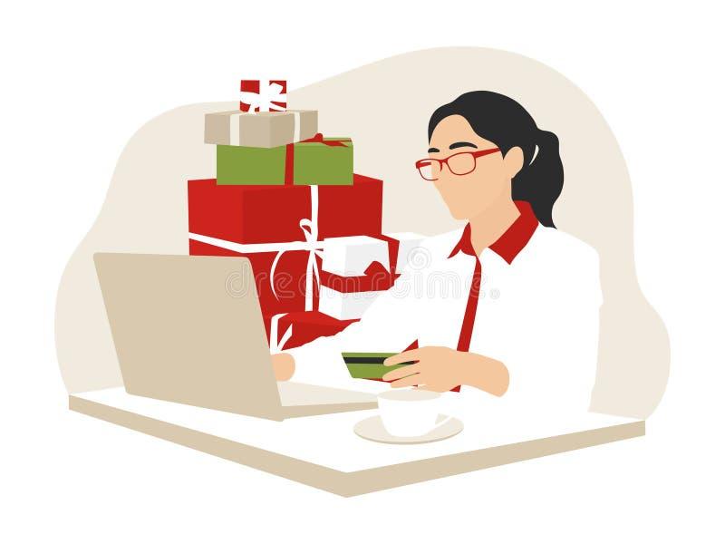 Mujer que hace compras en línea con un crédito o una tarjeta de débito para la Navidad fotos de archivo libres de regalías