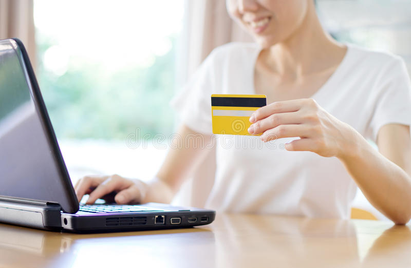 Mujer que hace compras en línea con una tarjeta de crédito y un teléfono fotos de archivo