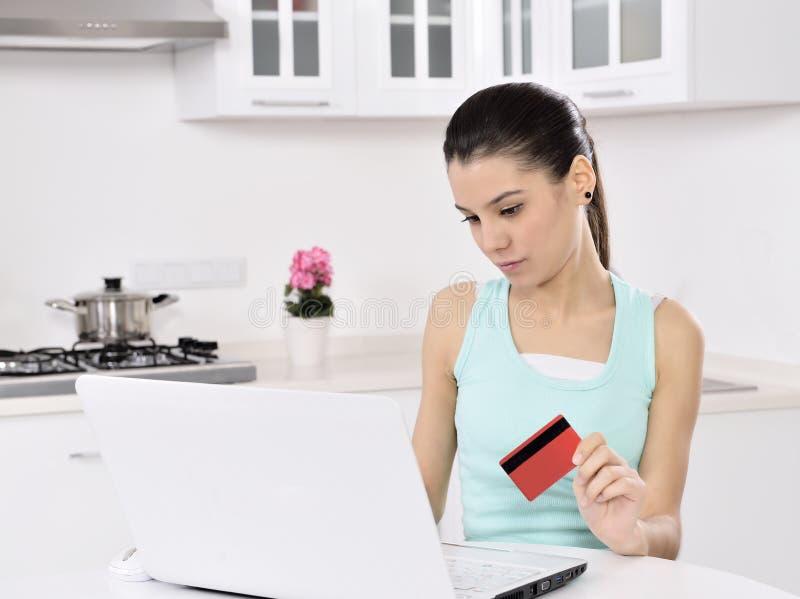 Mujer que hace compras en línea en casa imagen de archivo