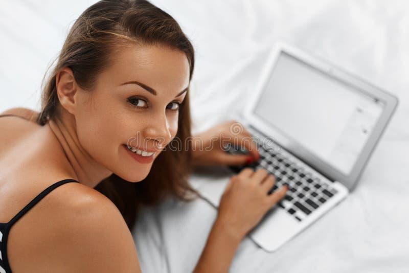 Mujer que hace compras en línea Muchacha sonriente que usa el ordenador portátil en casa fotos de archivo libres de regalías