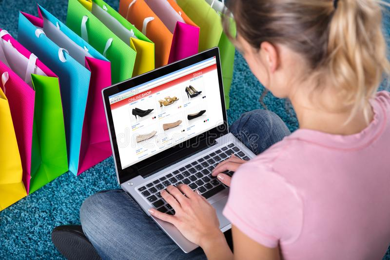 Mujer que hace compras en línea usando el ordenador portátil imagenes de archivo