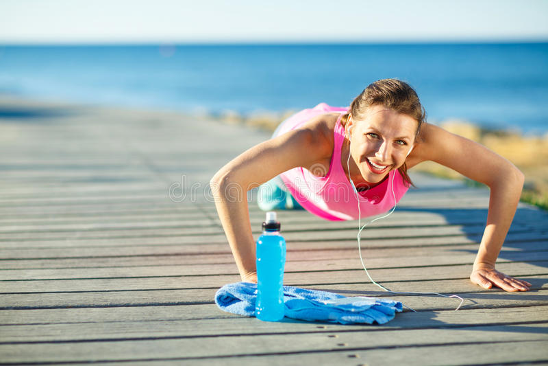 Mujer que hace deportes al aire libre en una trayectoria de madera en el mar fotografía de archivo