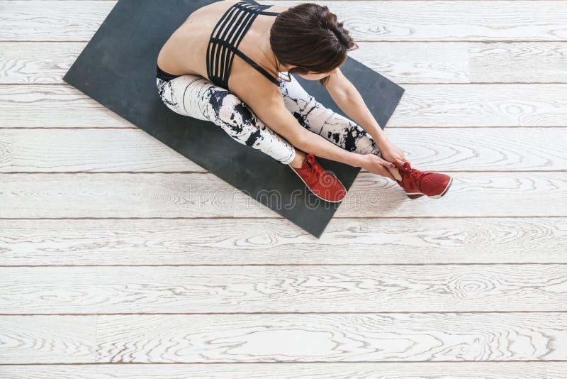 Mujer que hace ejercicio apto en el suelo blanco imagenes de archivo