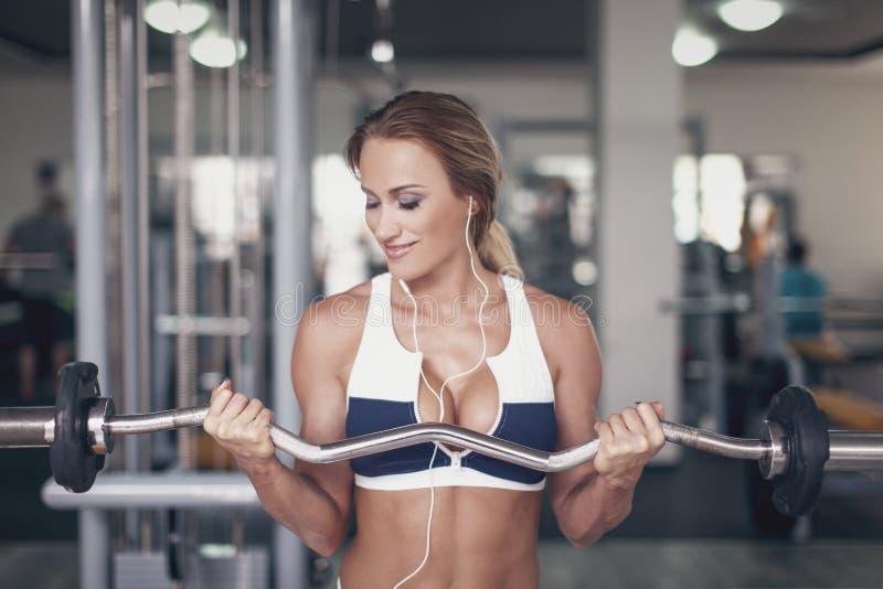 Mujer que hace ejercicio con la barra olímpica en gimnasio imagen de archivo libre de regalías