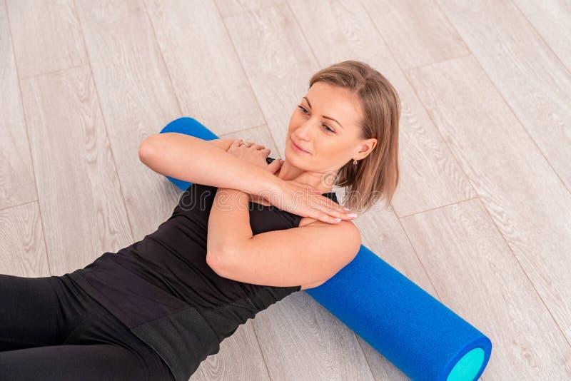 Mujer que hace ejercicio con un rodillo fotografía de archivo libre de regalías