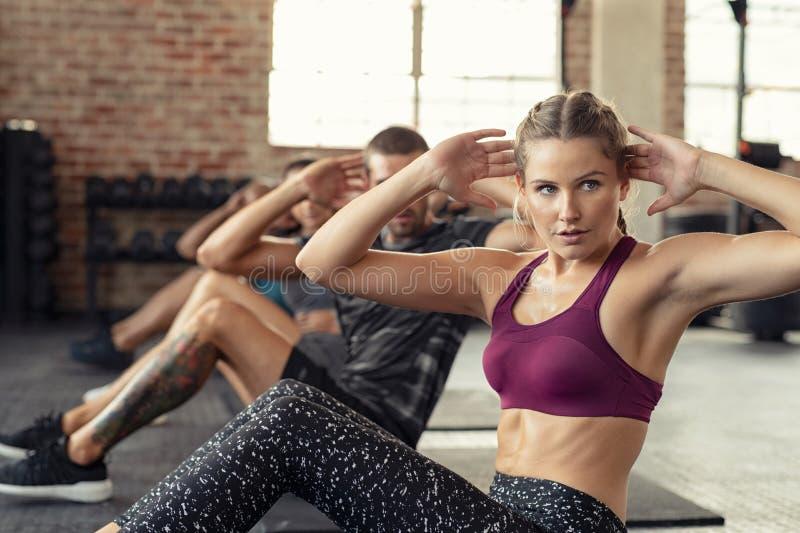 Mujer que hace ejercicio del ABS en el curso cardiio foto de archivo libre de regalías