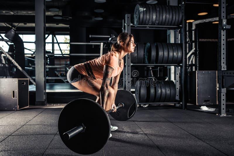 Mujer que hace ejercicio pesado del deadlift en gimnasio foto de archivo libre de regalías