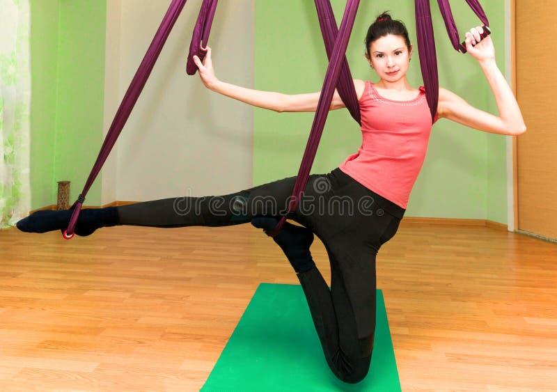 Mujer que hace ejercicios aéreos de la yoga en club imagen de archivo libre de regalías