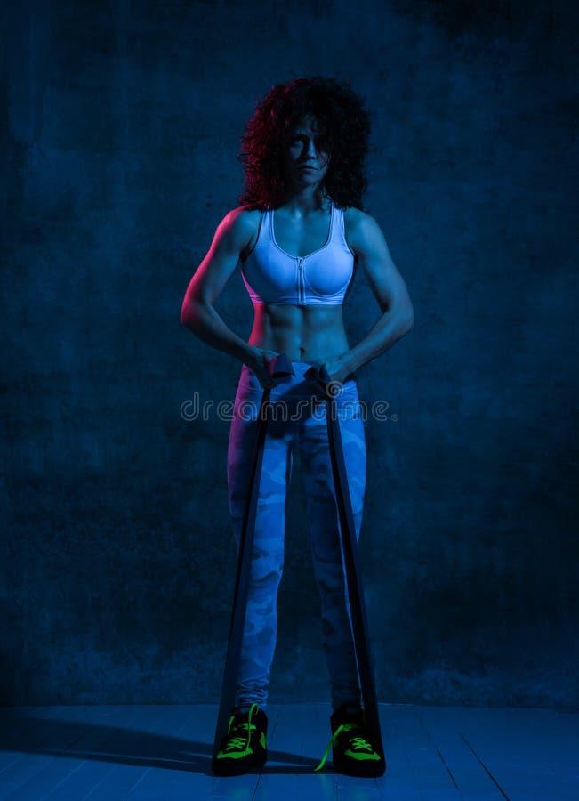 Mujer que hace ejercicios con el ampliador o la banda de la resistencia en gimnasio foto de archivo