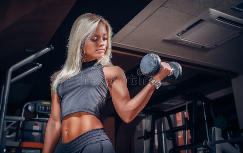 Mujer que hace ejercicios con pesa de gimnasia en el gimnasio fotografía de archivo
