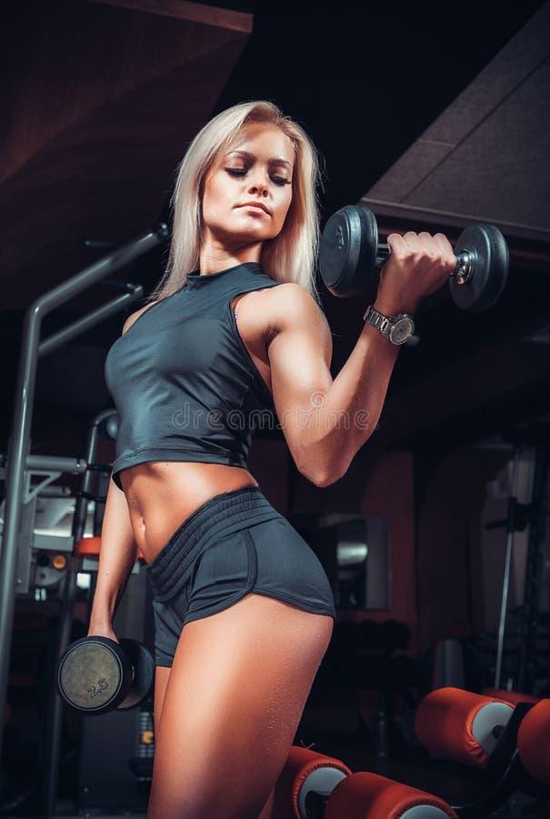 Mujer que hace ejercicios con pesa de gimnasia en el gimnasio imagen de archivo libre de regalías