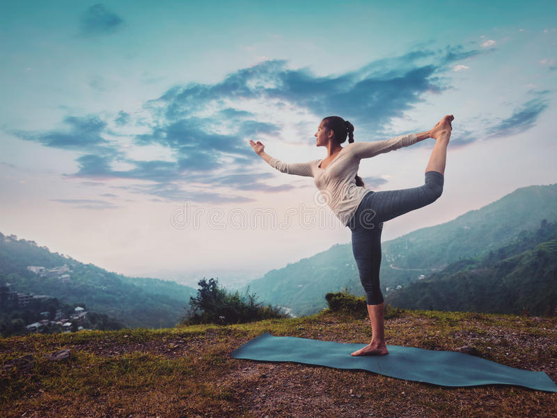 Mujer que hace el asana Natarajasana de la yoga al aire libre en puesta del sol imagen de archivo