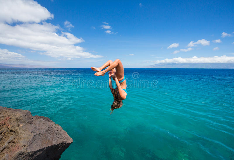 Mujer que hace el backflip en el océano fotos de archivo