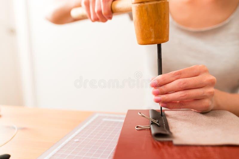 Mujer que hace el bolso de cuero foto de archivo libre de regalías