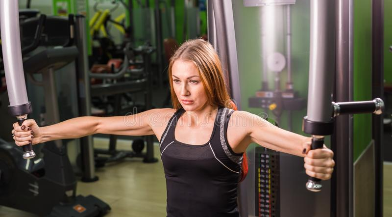 Mujer que hace el entrenamiento de la aptitud en una máquina de la mariposa con los pesos en un gimnasio foto de archivo