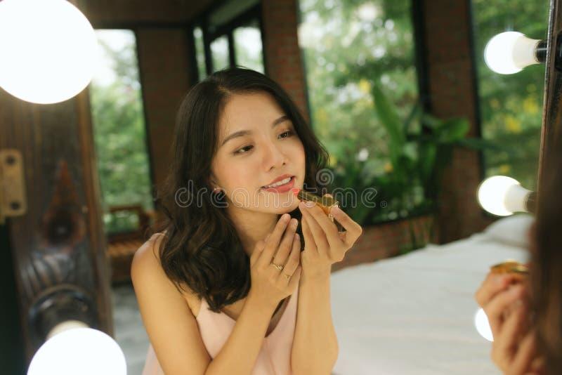 Mujer que hace el maquillaje, mujer joven hermosa que hace maquillaje y que sonr?e mientras que mira el espejo foto de archivo