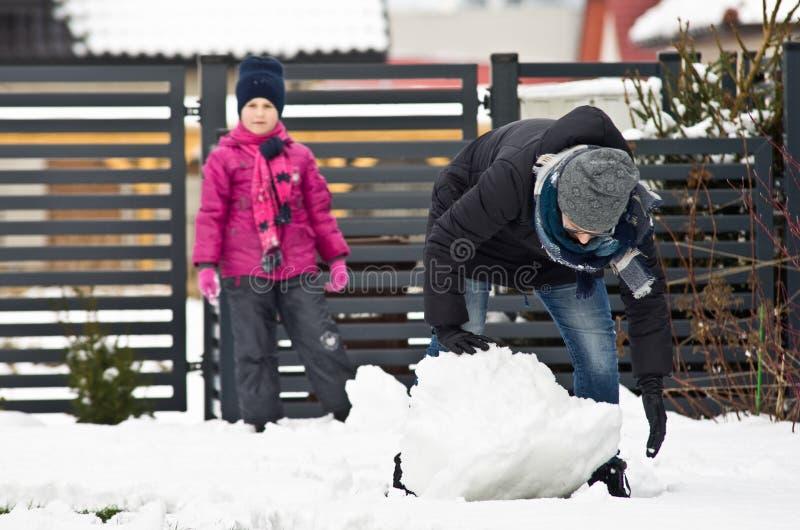 Mujer que hace el muñeco de nieve imagenes de archivo