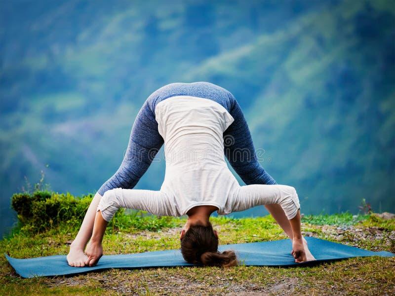 Mujer que hace el padottanasana de Prasarita del asana de la yoga de Ashtanga Vinyasa imagen de archivo
