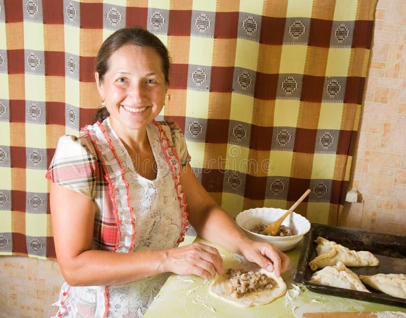 Mujer que hace el pastel de la carne fotografía de archivo libre de regalías