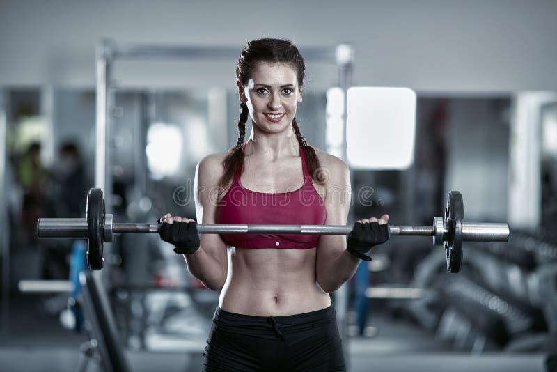 Mujer que hace el rizo del bíceps del barbell foto de archivo