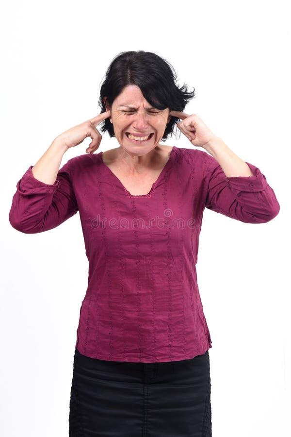 Mujer que hace el ruido que daña sus oídos en el fondo blanco imagen de archivo libre de regalías