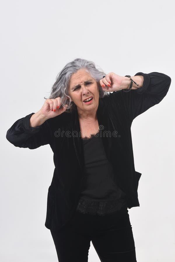 Mujer que hace el ruido que daña sus oídos en el fondo blanco fotos de archivo