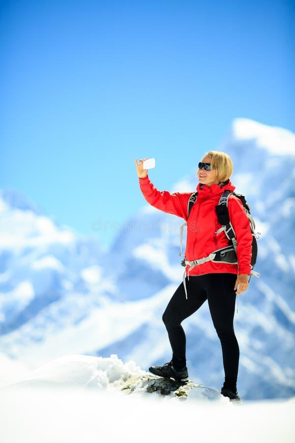 Mujer que hace el selfie del smartphone en montañas imagen de archivo libre de regalías
