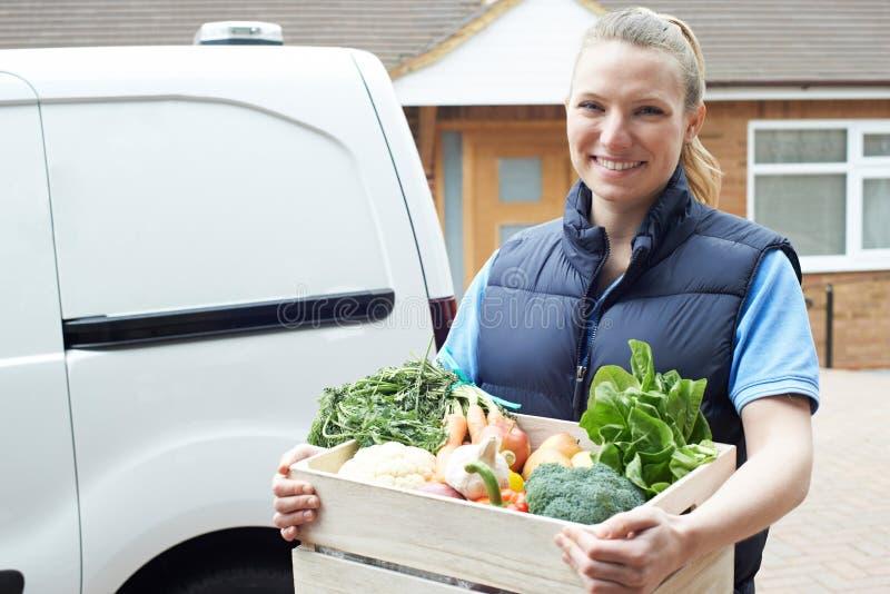 Mujer que hace el servicio a domicilio de la caja vegetal orgánica imagenes de archivo