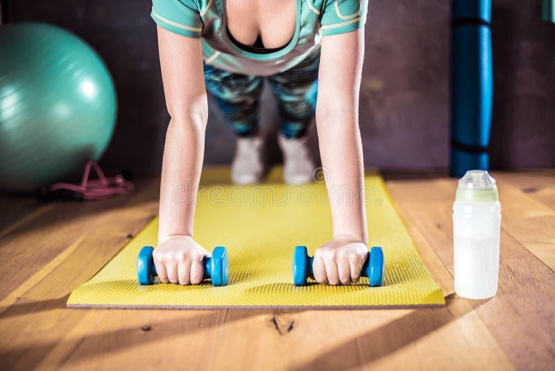 Mujer que hace entrenamiento en el gimnasio en las esteras de la yoga imágenes de archivo libres de regalías
