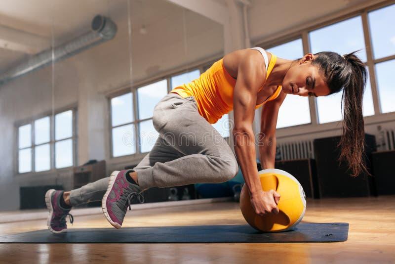 Mujer que hace entrenamiento intenso de la base en gimnasio foto de archivo