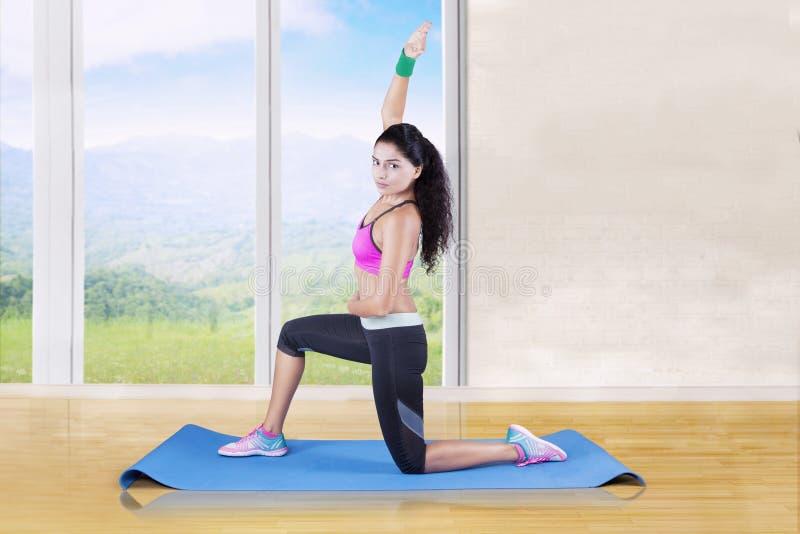 Mujer que hace estirando ejercicio en casa imagenes de archivo