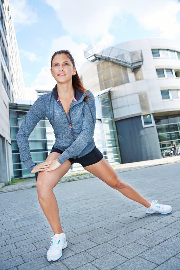 Mujer que hace estirando ejercicio en ciudad fotos de archivo libres de regalías