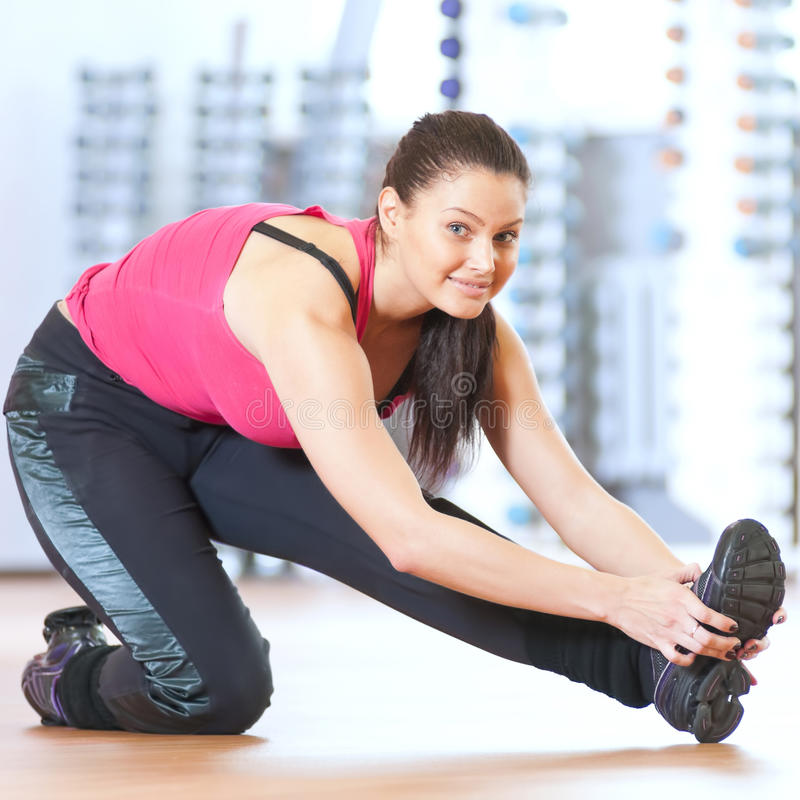 Mujer que hace estirando ejercicios en el gimnasio foto de archivo libre de regalías