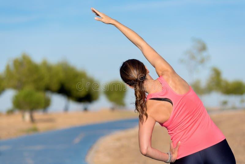 Mujer que hace estirando el ejercicio para la parte posterior, fondo del deporte foto de archivo