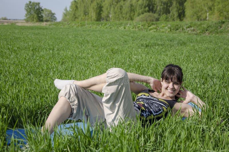 Mujer que hace estirar al aire libre en el campo imagen de archivo