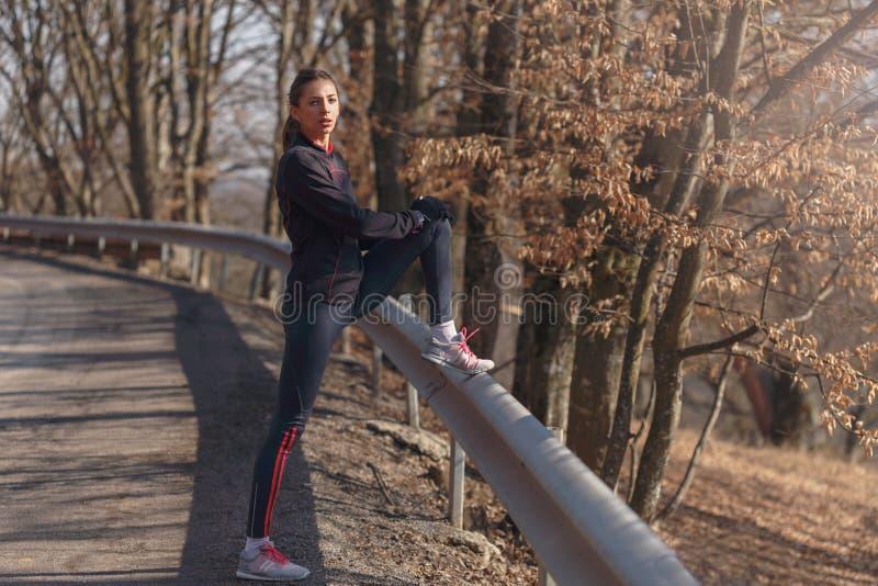 Mujer que hace estirar antes de activar en bosque imagen de archivo