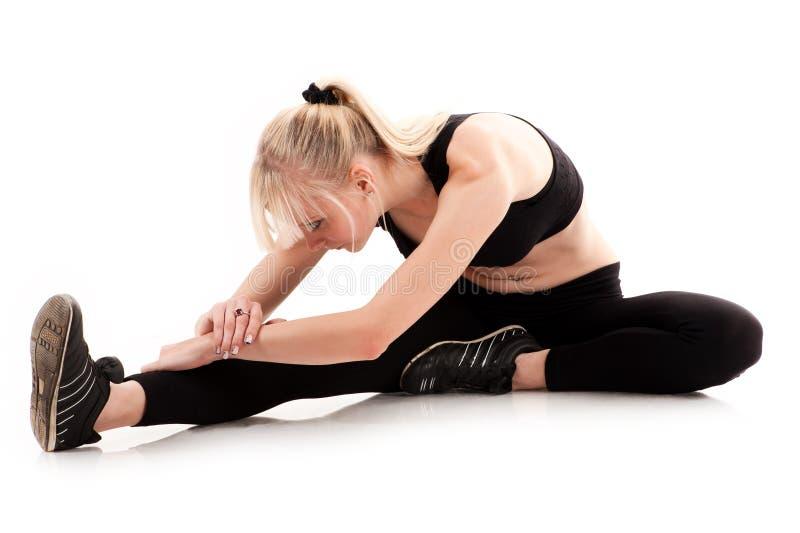 Mujer que hace estirar antes de ejercicio imagenes de archivo