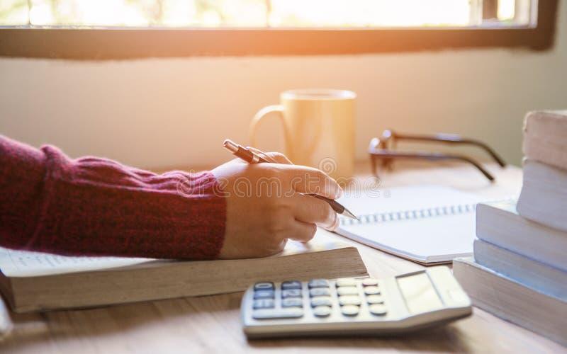 Mujer que hace finanzas y que calcula en oficina de la tabla en casa Finanzas y econom?a del concepto con el libro por ma?ana imágenes de archivo libres de regalías