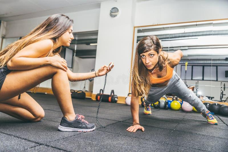 Mujer que hace flexiones de brazos en un gimnasio imagen de archivo libre de regalías
