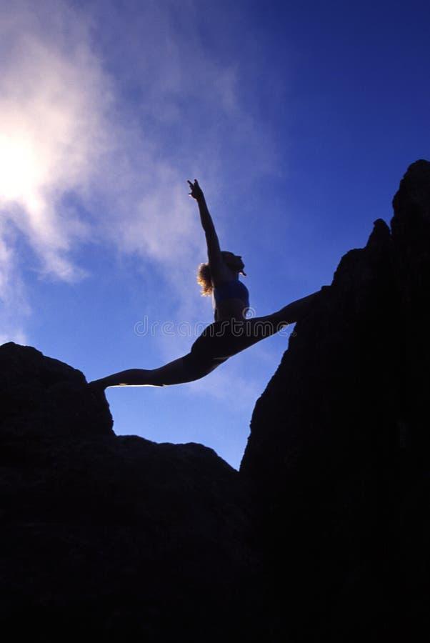 Mujer que hace fracturas en una cima de la montaña foto de archivo libre de regalías