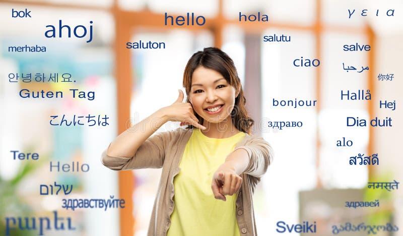 Mujer que hace gesto de la llamada de teléfono sobre palabras extranjeras imagen de archivo