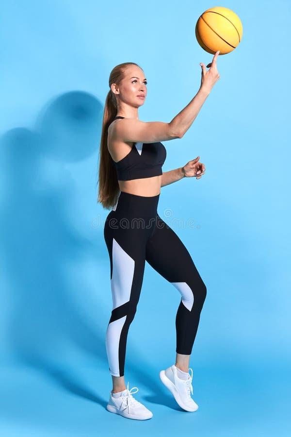 Mujer que hace girar un baloncesto en su finger aislado en fondo azul fotografía de archivo