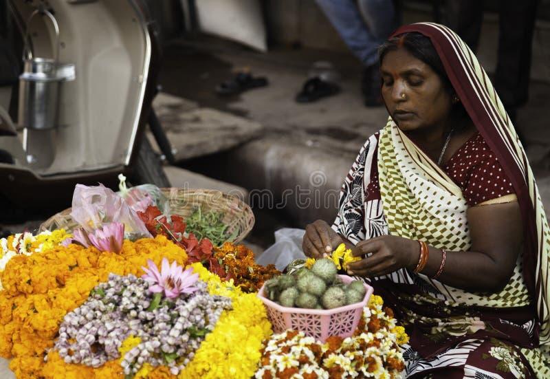 Mujer que hace guirnaldas de la flor en ella la parada fotografía de archivo libre de regalías