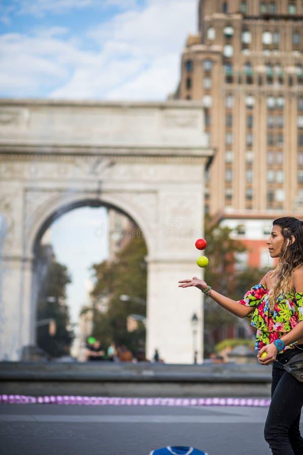 Mujer que hace juegos malabares con las bolas, en el medio del parque de Greenwich en el Ne imagen de archivo