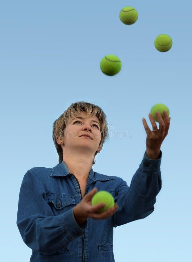 Mujer que hace juegos malabares con las pelotas de tenis fotografía de archivo